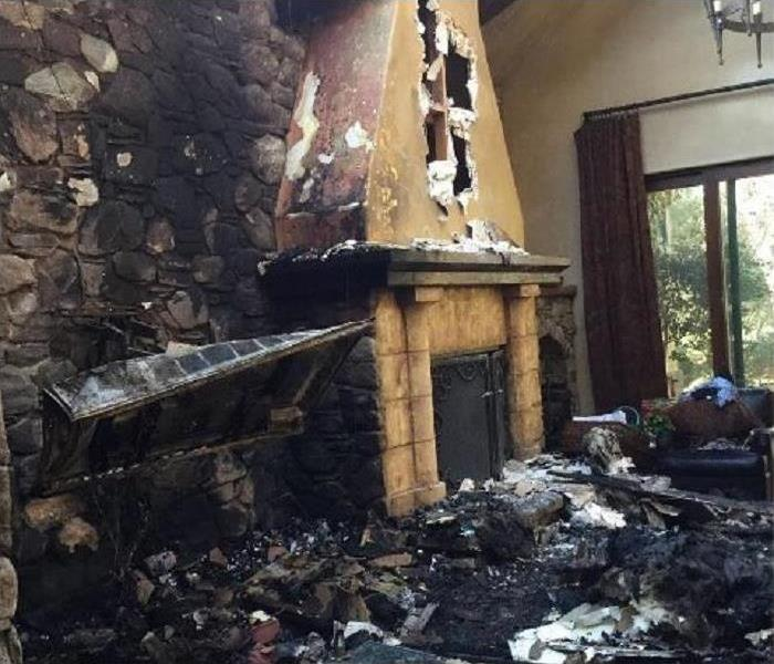 Fire place and living room devastated by fire damage with ash and soot everywhere