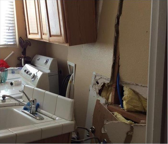 Laundry room wall showing considerable damage after a car crashed through it