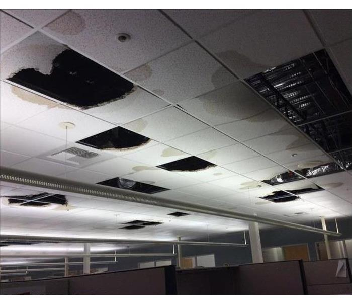 Business office ceiling with many panels fallen due to water damage
